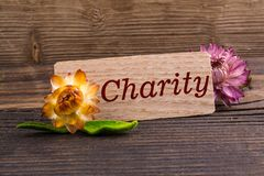 Charity word. On wooden card with dried flower on wood royalty free stock photography