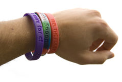 Charity wristbands cutout. Charity wristbands close-up on mans wrist Royalty Free Stock Image