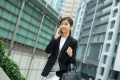 Charla asiática de la mujer de negocios en el teléfono móvil foto de archivo
