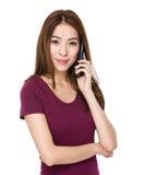 Charla asiática de la mujer joven en el teléfono móvil Foto de archivo