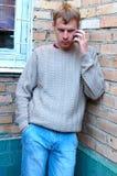 Charla con estilo joven del hombre sobre el teléfono móvil. Imagen de archivo