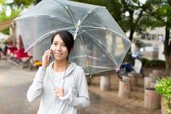 Charla de la mujer al teléfono móvil con el paraguas imagenes de archivo