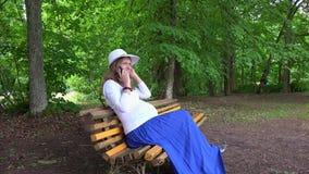 Charla de la mujer embarazada sobre el teléfono mientras que se sienta en banco de parque al aire libre almacen de metraje de vídeo