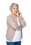 Charla de la mujer mayor en el teléfono móvil Imagen de archivo