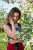 Charla de la mujer por el teléfono cerca del manzano Imagen de archivo