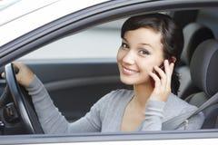 Charla de la mujer sobre el teléfono celular que se sienta en coche Imagenes de archivo