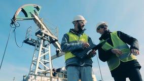 Charla de los trabajadores sobre un fondo de la torre de perforación de aceite Combustible fósil, concepto de la industria de pet almacen de video