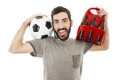 Charla del hombre joven sobre el teléfono móvil feliz y emocionado, sosteniendo la bola y el paquete de cerveza Foto de archivo libre de regalías