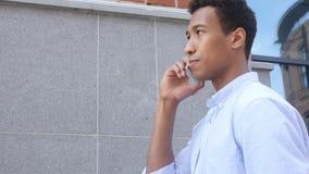 Charla del hombre negro joven, vista lateral del teléfono al aire libre almacen de video