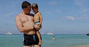 Charla del padre y del hijo sobre la playa almacen de video