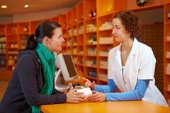 Charla discreta en farmacia Fotografía de archivo