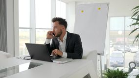 Charla ejecutiva feliz sobre smartphone al lugar de trabajo en el centro de negocios, conversación telefónica del jefe joven en o metrajes