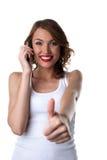Charla feliz de la mujer joven sobre el teléfono celular y los pulgares para arriba imagen de archivo