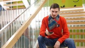 Charla joven acertada del hombre de negocios en el smarthphone metrajes