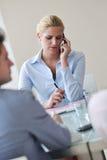 Charla joven de la mujer de negocios por el teléfono celular en meetng Imagen de archivo