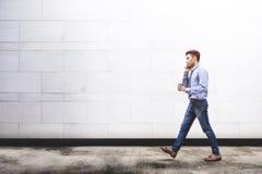 Charla joven del hombre de negocios de la motivación vía el teléfono elegante mientras que salga imágenes de archivo libres de regalías