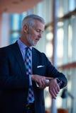 Charla mayor del hombre de negocios sobre el teléfono móvil Imagen de archivo