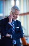Charla mayor del hombre de negocios sobre el teléfono móvil Foto de archivo