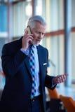 Charla mayor del hombre de negocios sobre el teléfono móvil Imagen de archivo libre de regalías