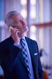 Charla mayor del hombre de negocios sobre el teléfono móvil Fotografía de archivo libre de regalías