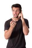 Charla muy enojada joven del hombre sobre el teléfono Imagenes de archivo