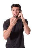 Charla muy enojada joven del hombre sobre el teléfono Foto de archivo libre de regalías