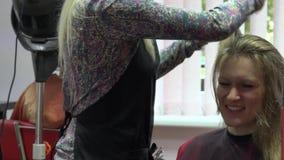 Charla rubia feliz de la mujer con su estilista personal mientras que hace corte de pelo 4K almacen de video