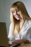 Charla rubia sonriente de la muchacha en línea Foto de archivo libre de regalías