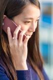 Charla sonriente hermosa de la mujer joven sobre el teléfono celular Imagenes de archivo
