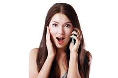 Charla sorprendida de la mujer sobre el teléfono Foto de archivo