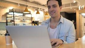 Charla video en café en el ordenador portátil por el hombre joven, hablando con los clientes almacen de metraje de vídeo