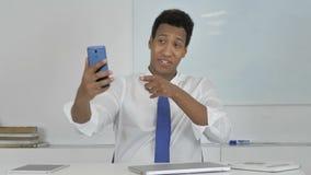 Charla video en línea del hombre de negocios afroamericano vía Smartphone metrajes