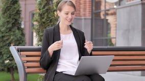 Charla video en línea en el ordenador portátil de la empresaria joven Sitting en banco almacen de metraje de vídeo