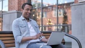 Charla video en línea en el ordenador portátil por el hombre africano que se sienta en banco metrajes