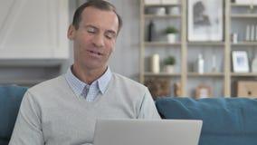 Charla video en línea en el ordenador portátil por el hombre envejecido medio que se sienta en el lugar de trabajo creativo almacen de video