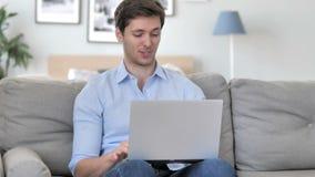 Charla video en línea en el ordenador portátil por el hombre joven hermoso que se sienta en el lugar de trabajo creativo almacen de video