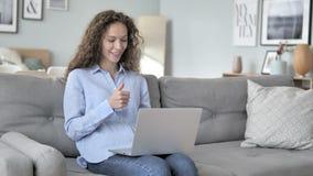 Charla video en línea en el ordenador portátil por la mujer del pelo rizado que se sienta en el lugar de trabajo creativo metrajes