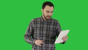 Charla video en línea en la tableta caminando al hombre en una pantalla verde, llave de la croma almacen de metraje de vídeo