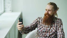 Charla video que habla del hombre de negocios joven barbudo del inconformista en smartphone mientras que se sienta en silla del o Foto de archivo