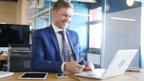 Charla video sonriente de Having Relax Online del hombre de negocios en oficina Fotografía de archivo