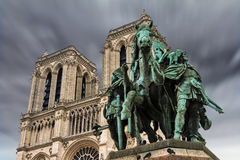 Charlemagne. The bronze equestrian statue Charlemagne et ses Leudes (Charlemagne and his guards) in front of Notre Dame Cathedral with an ominous sky Royalty Free Stock Photo