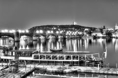 Charles Bridge and the center of Prague on a night black and white HDR photo and with a boat in the foreground Stock Photo
