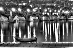 Charles Bridge and the center of Prague on a night black and white HDR photo and with a boat in the foreground Royalty Free Stock Images