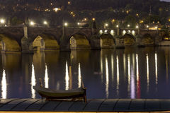 Charles Bridge and the center of Prague on a night HDR photo and with a boat in the foreground Royalty Free Stock Image