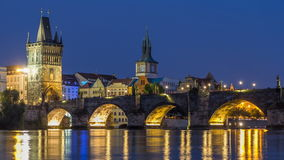 The Charles Bridge day to night timelapse over the Vltava River reflected in water in Prague, Czech Republic stock footage