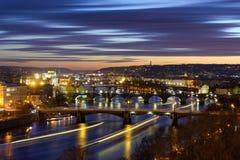 Charles Bridge durante il tramonto con parecchie barche, Praga, repubblica Ceca Immagine Stock