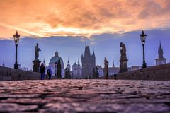 Charles Bridge en la ciudad vieja de Praga en la salida del sol con el cielo dramático Foto de archivo