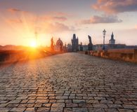 The Charles Bridge Karluv Most and Old Town Tower during amazing sunrise when haze occur. View of morning dramatic cloudy sky. P Royalty Free Stock Photography