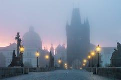 Charles Bridge in Prague at sunrise at morning in fog Royalty Free Stock Images