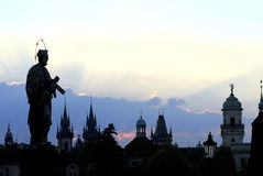 Charles Bridge Series. St John Nepomuk and the spires of the Old Town in the morning sun rise Royalty Free Stock Photos